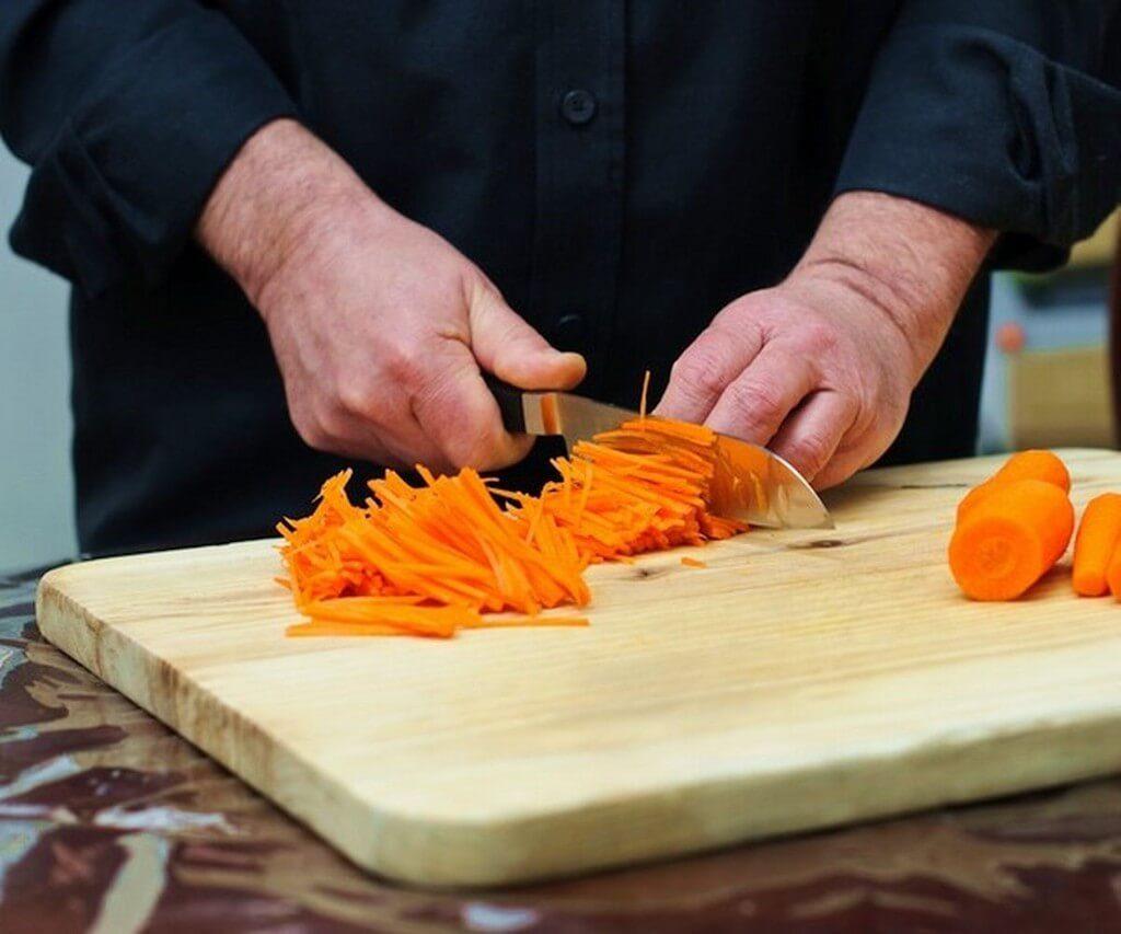мужчина шинкует морковку